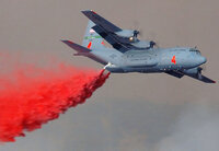 A C-130 dropping fire retardant on a fire in Southern California.