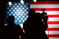 News camera operators silhouetted against an American flag