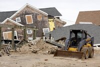 Tractor in front of homes devastated by Hurricane Sandy