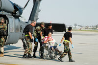 A woman in a wheelchair is evacuated via helicopter following Hurricane Katrina.