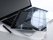 A smartphone and a tablet stacked on top of a laptop to depict mobility and BYOD, bring your own device