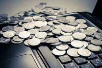 Coins on a laptop to represent investment in technology