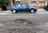 Photo of car and pothole for story on SeeClickFix