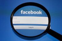 A magnifying glass hovers over a facebook login screen