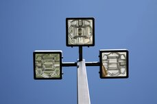 Three LED lights on a pole, against a blue sky.