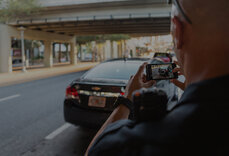 A police officer taking a picture of a license plate using a cell phone