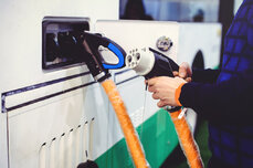 Close-up of operator plugging chargers into the side of an electric bus