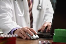 A doctor using a laptop computer.