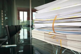 Paper files stacked on a desk to represent transcripts