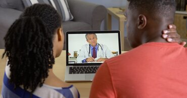 A doctor meeting virtually with two people.