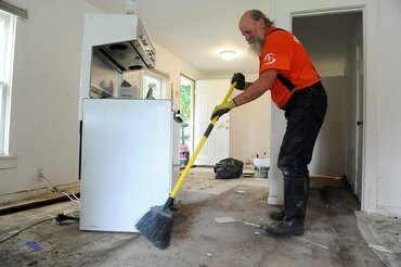 Samaritan, Ed Shank sweeps a flooded home in Texas.