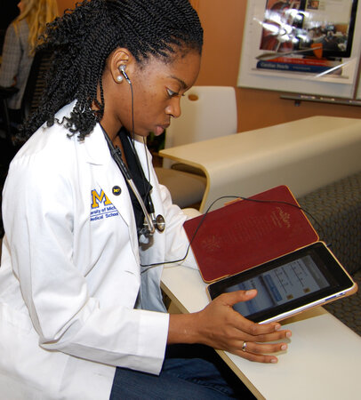 A medical student looks at her tablet.