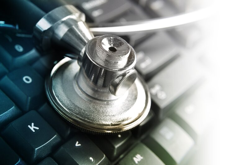 A closeup of a medical stethoscope on top of a computer keyboard.