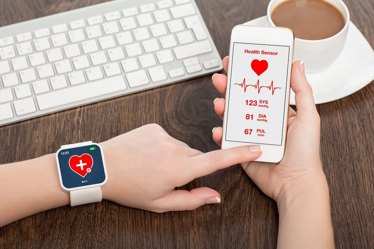 A woman holding a smartphone and smartwatch with mobile app health sensor.