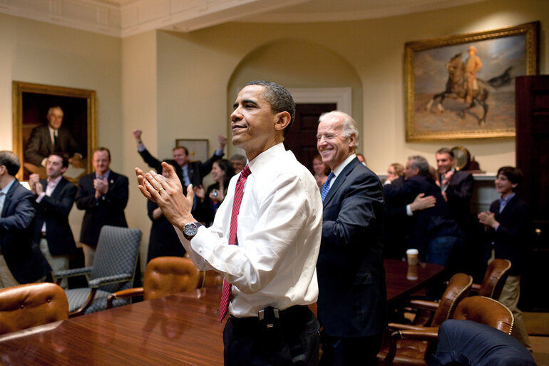President Barack Obama, Vice President Joe Biden, and senior staff, react in the Roosevelt Room of the White House as the House passes the health care reform bill, March 21, 2010.