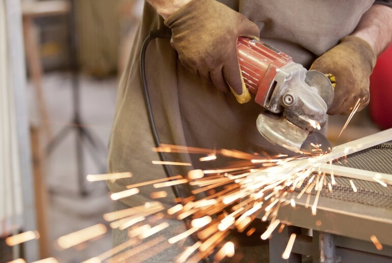 Gloved blue collar worker grinding material with sparks