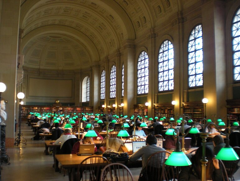 Many people studying at tables at the McKim Building at Boston Public Library.
