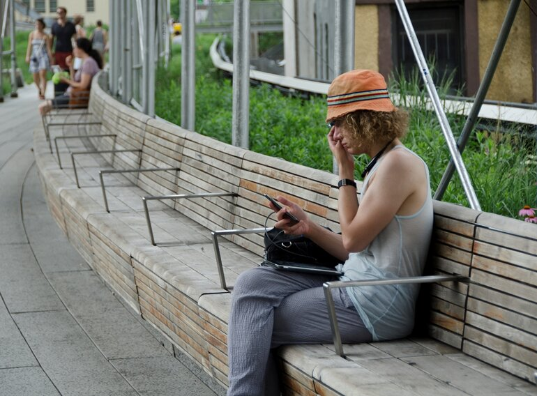 person on a bench uses Google Glass