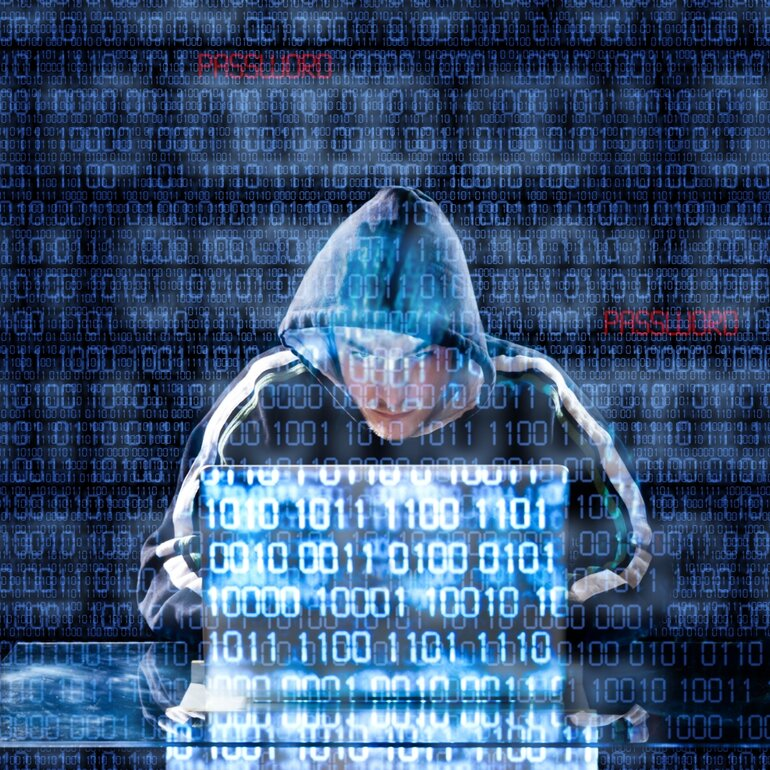 Hooded hacker on a laptop with binary code to represent data breaches