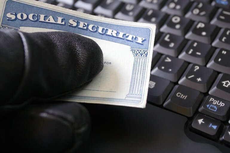 Gloved hand holding a social security card over a computer keyboard