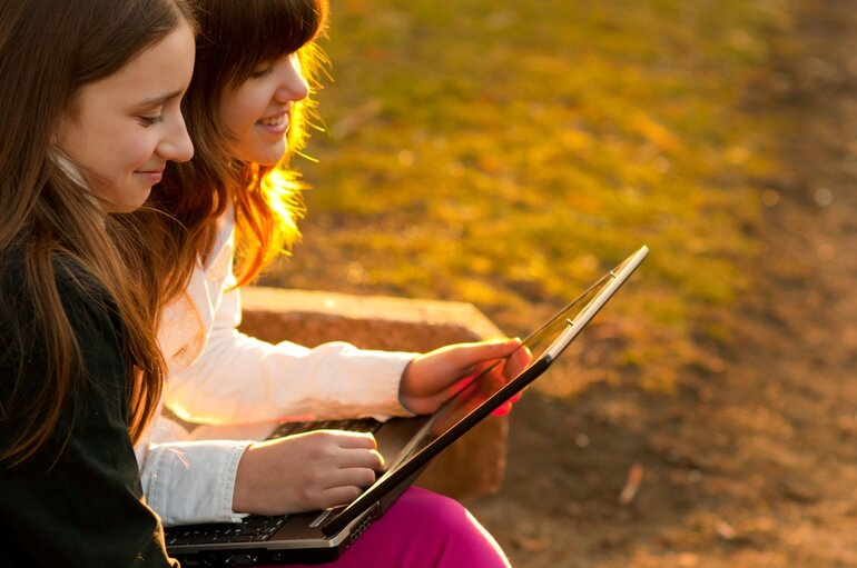 Two young girls on a laptop outside