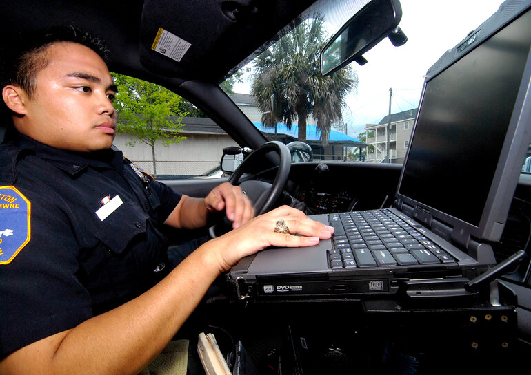 Police officer on a laptop in a patrol car