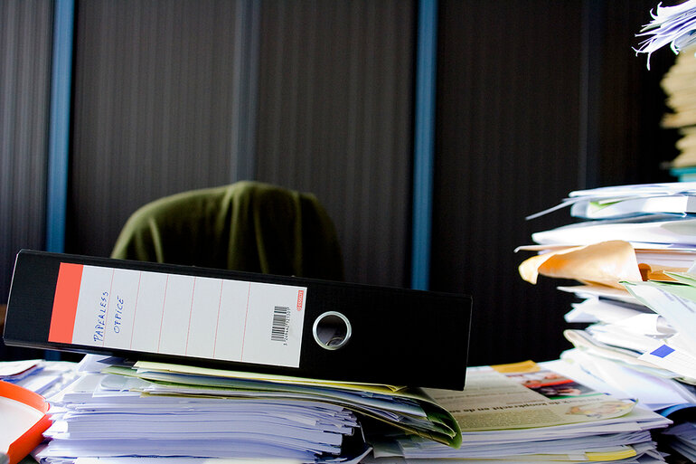 Stacks of papers, files and a binder labeled paperless office on a desk