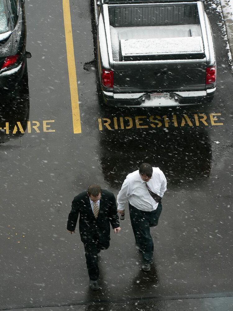 Two men walk in a parking lot with rideshare parking spaces