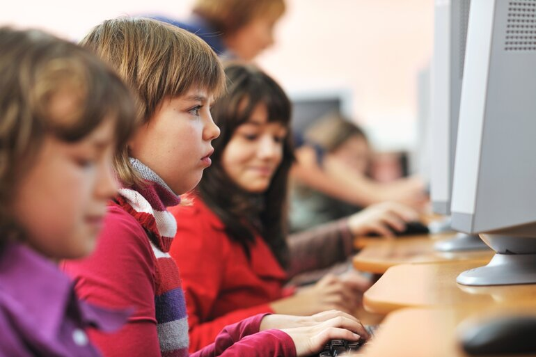 Elementary school age kids working at computers
