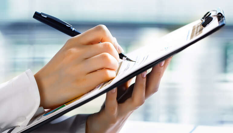 Closeup of someone taking a survey on a clipboard