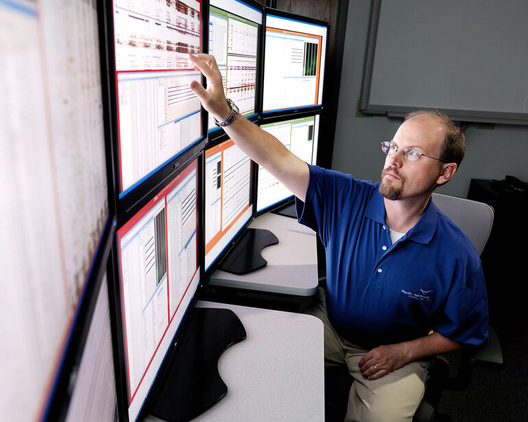 Big data represented by a man interacting with multiple computer screens.