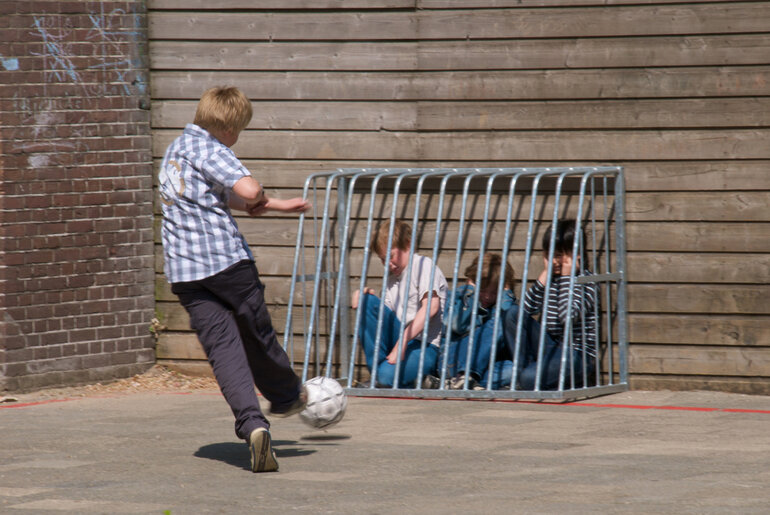 A child torments three others by kicking a soccer ball at them.