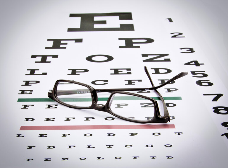 Glasses sitting on an eye chart.