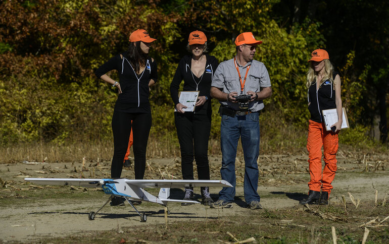 "Three PETA ""Air Angels"" speak with a drone operator during a demonstration."
